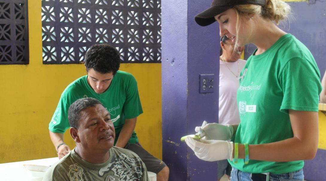 On the Projects Abroad Public Health internship for teenagers in Belize, a student and local man talk.